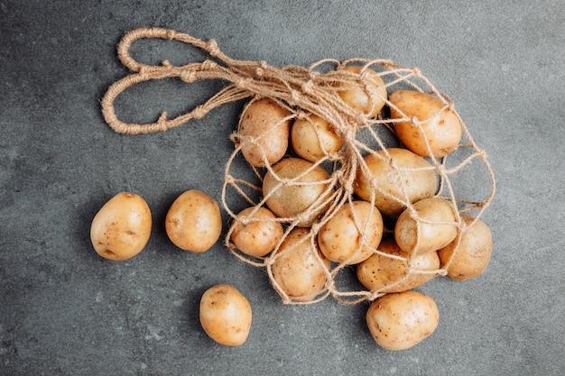 Batatas em um saco líquido em um fundo escuro e texturizado. configuração plana.