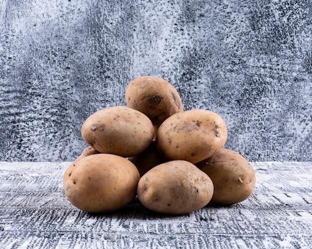Batatas em um saco saco vista lateral em uma mesa de madeira cinza