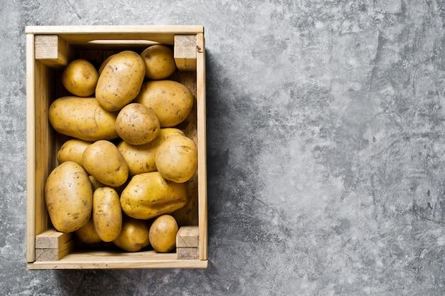 Batatas em uma caixa de madeira, supermercado.