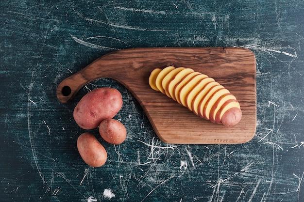 Batatas em uma placa de madeira e no copo, vista superior.