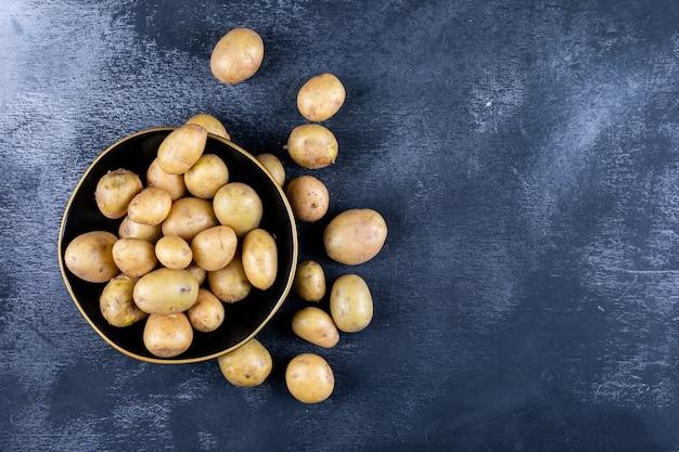 Batatas em uma tigela e ao redor, em uma mesa escura