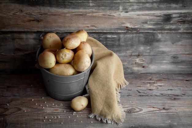 Batatas em uma vista lateral de balde cinza em um espaço de fundo escuro de madeira para texto