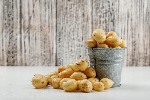 Batatas em uma vista lateral de mini balde na parede de madeira branca e suja