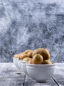 Batatas em uma vista lateral de tigelas em uma mesa de madeira cinza
