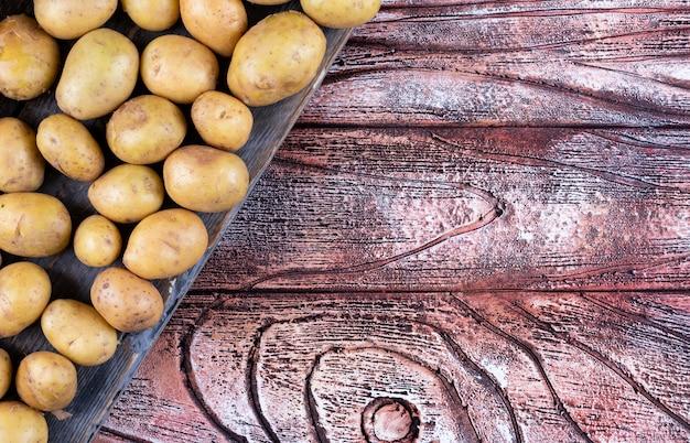 Batatas em uma vista superior de pano em uma mesa de madeira
