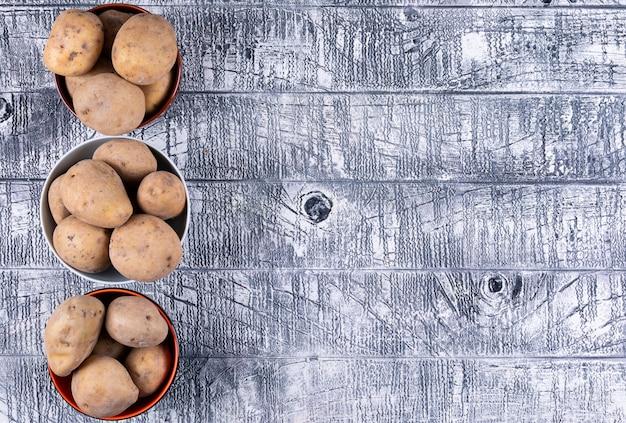 Batatas em uma vista superior de tigelas em uma mesa de madeira cinza