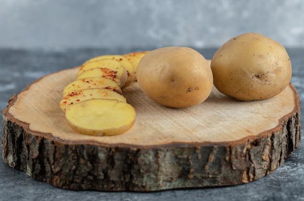 Batatas fatiadas e inteiras na tábua de madeira