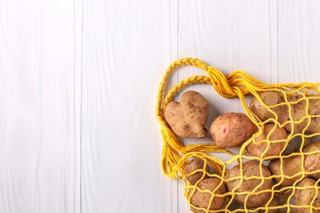 Batatas feias orgânicas em uma sacola têxtil amarela em fundo branco, orientação horizontal, conceito de desperdício zero, espaço de cópia