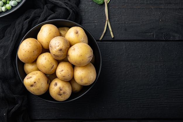 Batatas frescas com casca, pequenas, planas, sobre fundo preto de madeira com espaço para texto