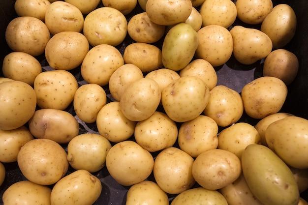 Batatas frescas cruas com casca, inteiras, muitas empilhadas a granel, no mercado de alimentos.