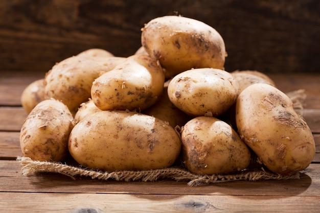 Batatas frescas cruas em uma mesa de madeira