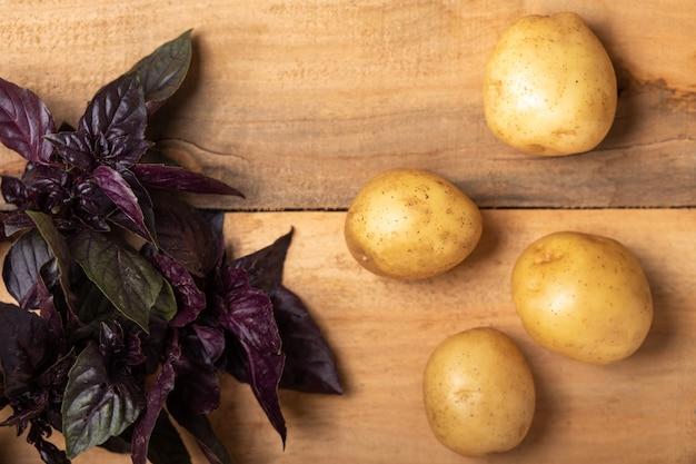Batatas frescas cruas em uma superfície de madeira