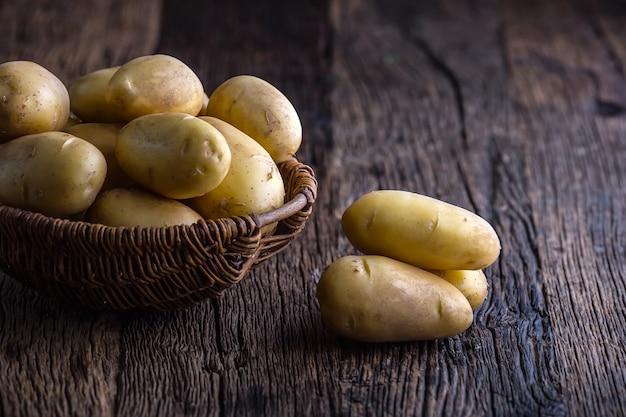 Batatas frescas cruas na cesta na placa de carvalho rústica.