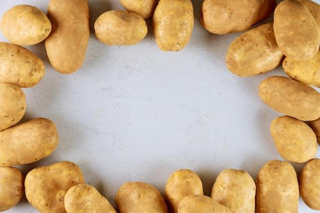 Batatas frescas cruas na superfície branca