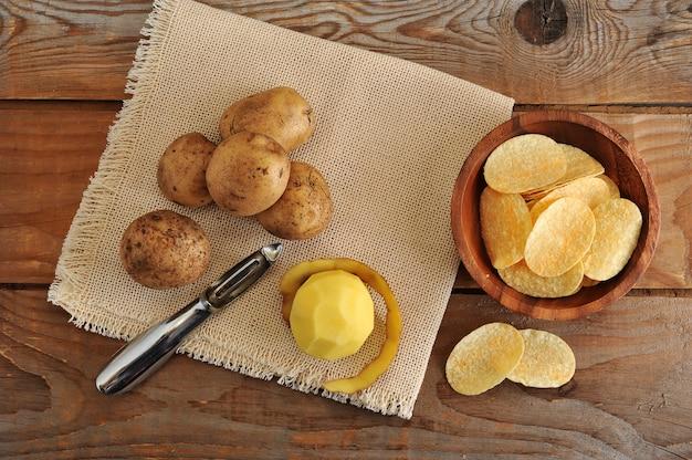 Batatas frescas, descascador de batatas e batatas fritas