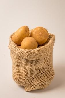 Batatas frescas e cruas em um saco rústico isolado no branco
