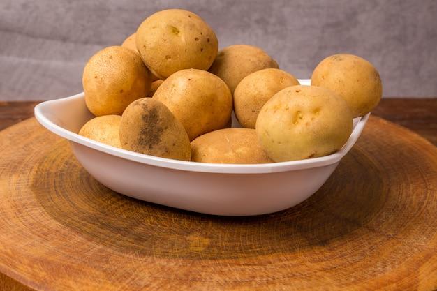 Batatas frescas e cruas empilhadas em um prato redondo na mesa de madeira.
