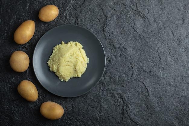 Batatas frescas e purê de batatas. vista do topo. fundo preto.