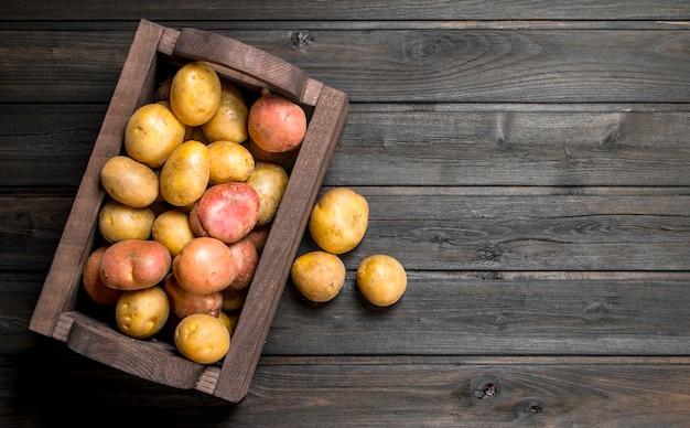 Batatas frescas em uma caixa de madeira. em fundo de madeira