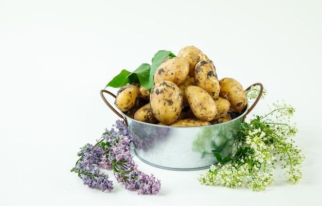 Batatas frescas em uma panela de metal com flores e folhas vista lateral