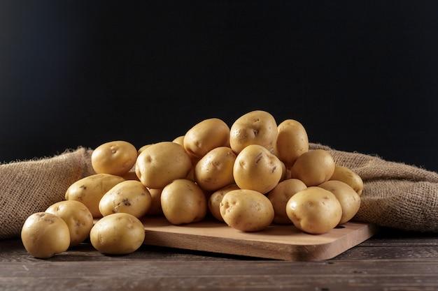 Batatas frescas no fundo madeira