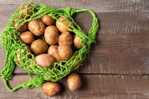 Batatas frescas no saco de compras reusável da malha do desperdício zero do eco sobre o fundo branco, orientação horizontal.
