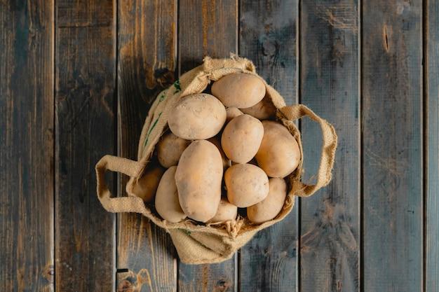 Batatas frescas sujas no saco de pano isolado na superfície de madeira b