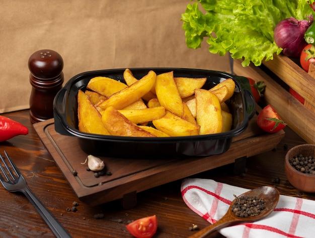 Batatas fritadas com o takeaway das ervas no recipiente preto.