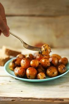 Batatas fritas assadas com casca em um prato.
