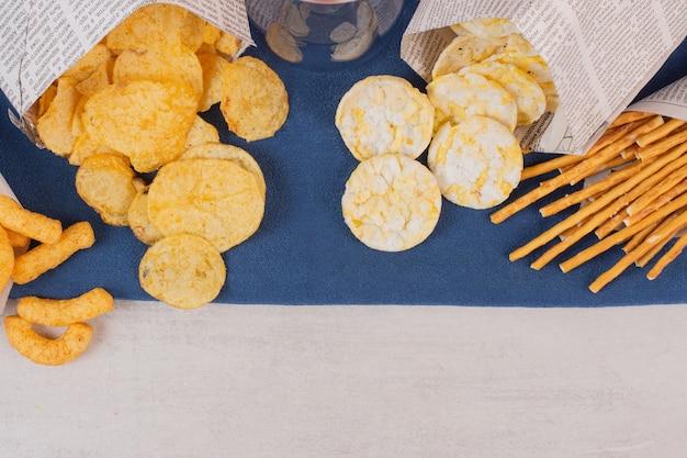 Batatas fritas, biscoitos e pretzels na toalha de mesa azul.