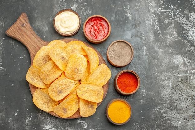 Batatas fritas caseiras, especiarias e maionese com ketchup na tábua de madeira na mesa cinza