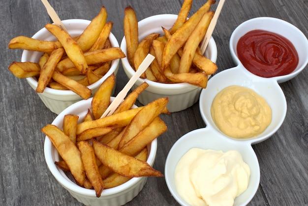 Batatas fritas caseiros em tigelas para lanches e molhos em fundo de madeira.