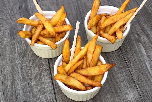 Batatas fritas caseiros em umas bacias para petiscos no fundo de madeira.