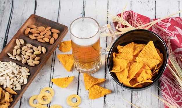 Batatas fritas, cerveja e frutas secas em cima da mesa