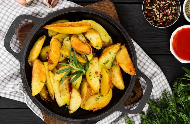 Batatas fritas com alecrim fresco em panela de ferro fundido, estilo rústico.