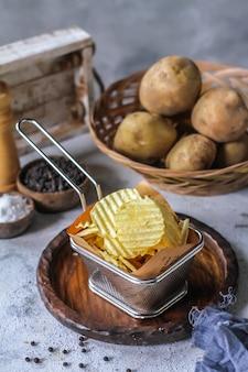 Batatas fritas com batata crua na mesa de madeira