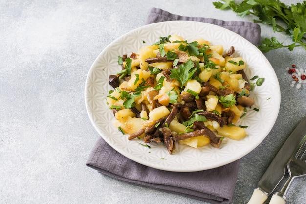 Batatas fritas com cogumelos e ervas frescas. copie o espaço
