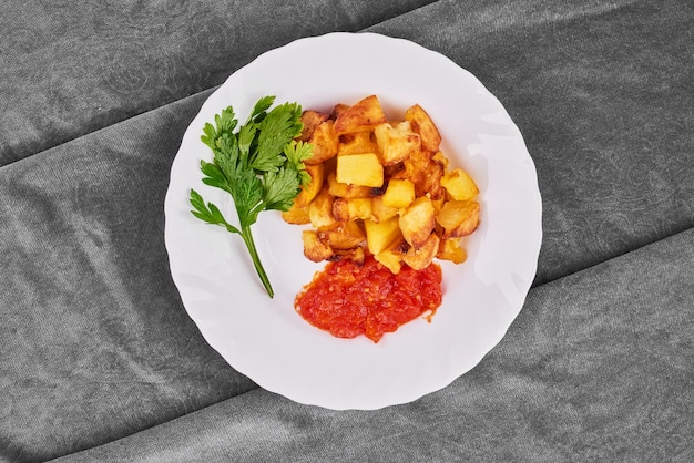 Batatas fritas com extrato de tomate e ervas.