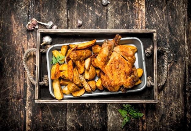 Batatas fritas com frango na bandeja na mesa de madeira.