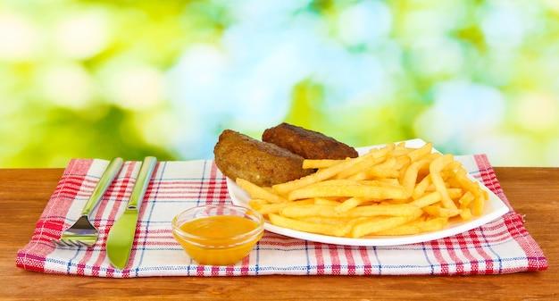 Batatas fritas com hambúrgueres no prato verde