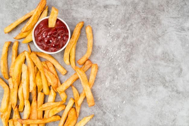 Batatas fritas com ketchup e cópia espaço