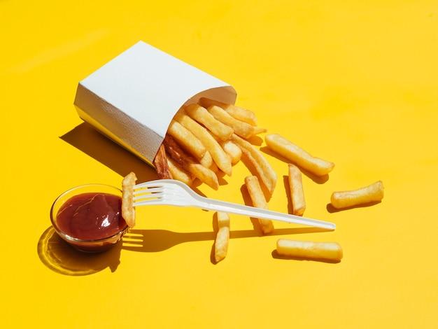 Batatas fritas com ketchup e garfo de plástico