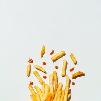Batatas fritas com ketchup em fundo cinza