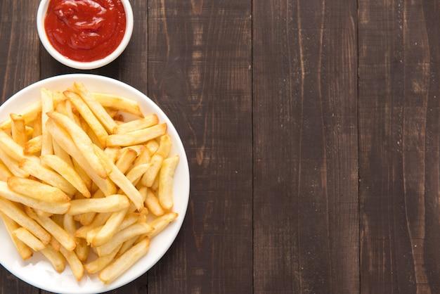 Batatas fritas com ketchup em fundo de madeira