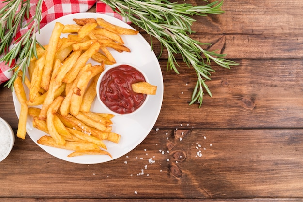 Batatas fritas com ketchup gostoso na mesa de madeira