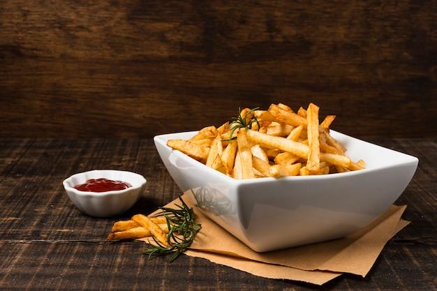 Batatas fritas com ketchup na mesa de madeira