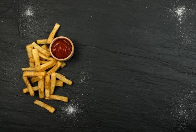 Batatas fritas com ketchup na mesa escura