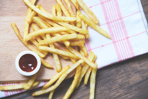 Batatas fritas com ketchup na placa de madeira