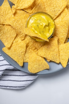 Batatas fritas com molho de queijo no prato cinza e guardanapo listrado na mesa branca, vista superior. foto de comida mexicana, vertical. lanches nachos close-up, acima