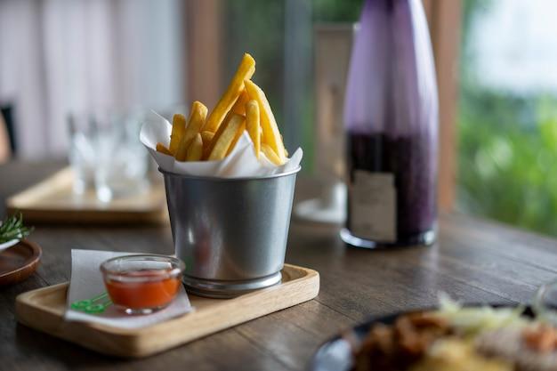 Batatas fritas com molho de tomate colocado sobre a mesa